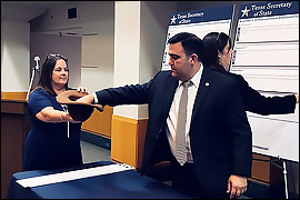 Deputy Secretary Esparza placing his hand into a hat to randomly draw a proposition to determine the order.