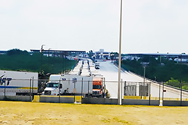 There is an extremely long line of trucks on the international bridge.