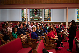 Secretary Whitley sitting in a church with other NASS members.