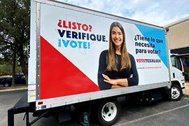 Side view of a truck that says, Ready, Check. Vote. in Spanish.